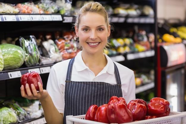 Retrato de un trabajador rubio sonriente tomando verduras