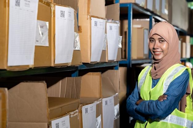 Retrato de la trabajadora del almacén musulmana del islam cruzó el brazo delante del estante del producto con la tarjeta de stock en el entorno de distribución del almacén. para el inventario de almacén comercial y el concepto logístico.