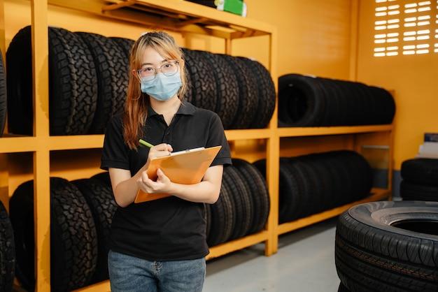 Retrato de trabajadora asiática usa una máscara para evitar la propagación del virus corona o covid-19 comprobando el stock de neumáticos de automóvil en el almacén
