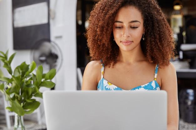 Retrato de trabajadora autónoma afroamericana ocupada centrada en la computadora portátil, satisfecha con el éxito del negocio en línea, trabaja duro para lograr el éxito