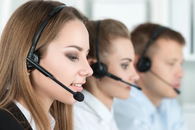 Retrato de trabajadora de call center acompañada de su equipo. operador de soporte al cliente sonriente en el trabajo. concepto de ayuda y soporte
