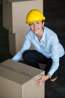 Retrato de trabajadora de fábrica recogiendo cajas de cartón