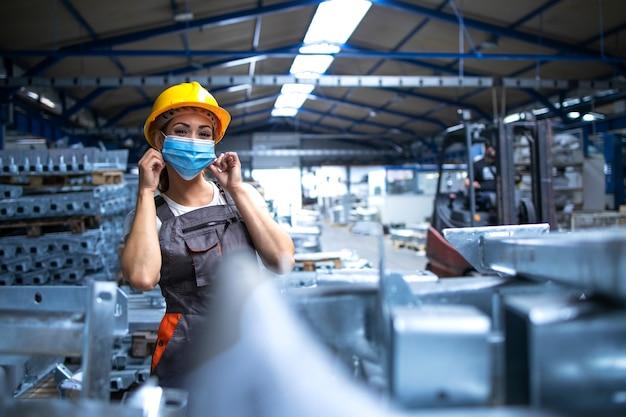Retrato de trabajadora de fábrica en uniforme y casco con máscara facial en la planta de producción industrial