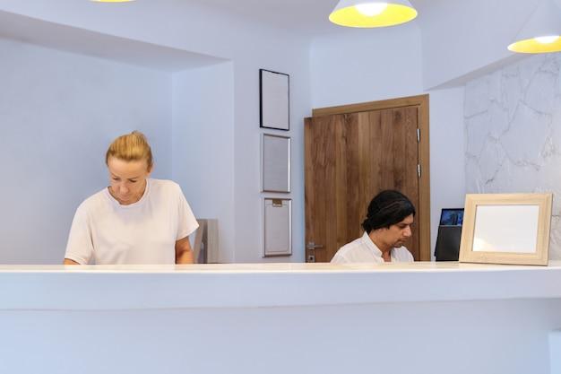 Retrato de los trabajadores del hotel en el lugar de trabajo, recepcionistas de hombre y mujer cerca de recepción