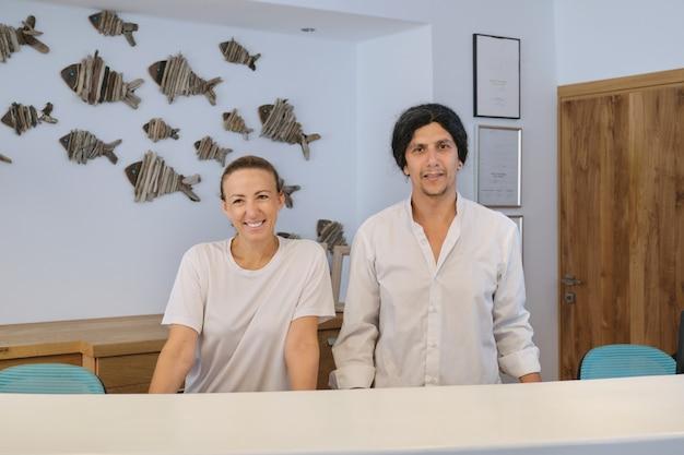 Retrato de trabajadores del hotel spa, hombre y mujer cerca de recepción