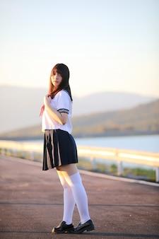 Retrato de traje de colegiala japonesa asiática mirando el parque al aire libre en la salida del sol