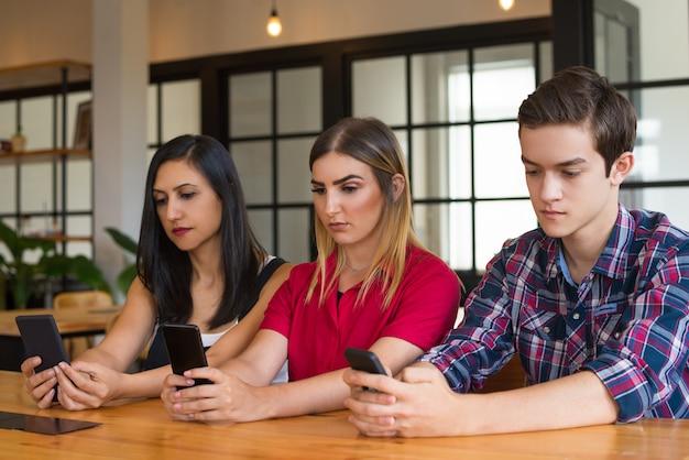 Retrato de tres adolescentes o estudiantes utilizando teléfonos móviles.