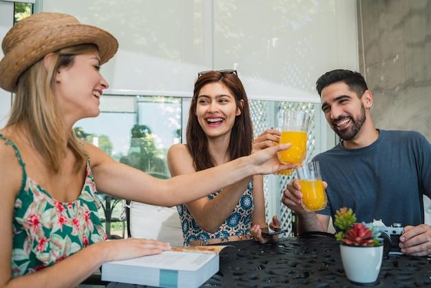 Retrato de tres amigos viajeros que pasan un rato y organizan su viaje en el hotel. concepto de viajes y estilo de vida.