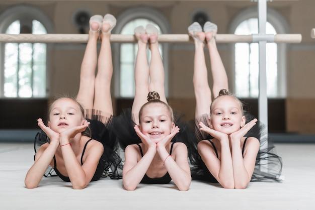 Retrato de tres chicas bailarina poising delante de la barra