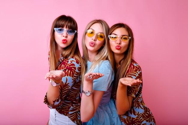 Retrato de tres chicas súper excitadas de mejores amigas, vibraciones positivas y felices, ropa y accesorios de moda con estampado tropical brillante de verano, pared rosa, hermanas divirtiéndose.