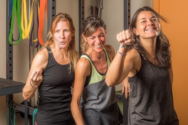 Retrato de tres deportistas mostrando los puños cerrados de manera divertida en el gimnasio. concepto de personas en el gimnasio.