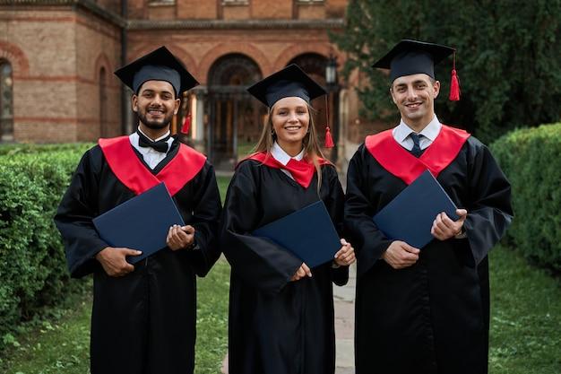 Retrato de tres estudiantes internacionales femeninos y masculinos con diplomas celebrando la graduación en el campus universitario.