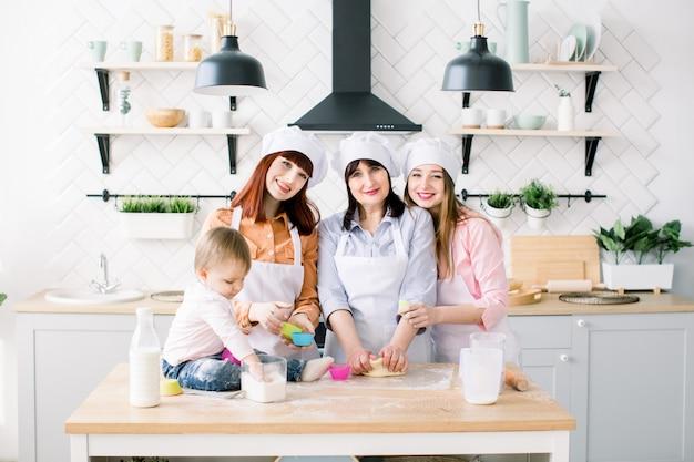 Retrato de tres generaciones de mujeres horneando cupcakes en la cocina. la familia feliz junta ama la armonía, la cocina navideña y el concepto del día de la madre.