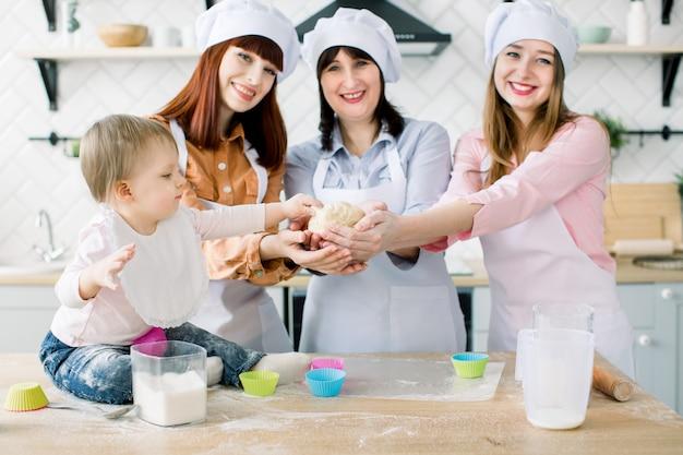 Retrato de tres generaciones de mujeres horneando cupcakes en la cocina, pequeña niña jugando con masa. la familia feliz junta ama la armonía, la cocina navideña y el concepto del día de la madre.