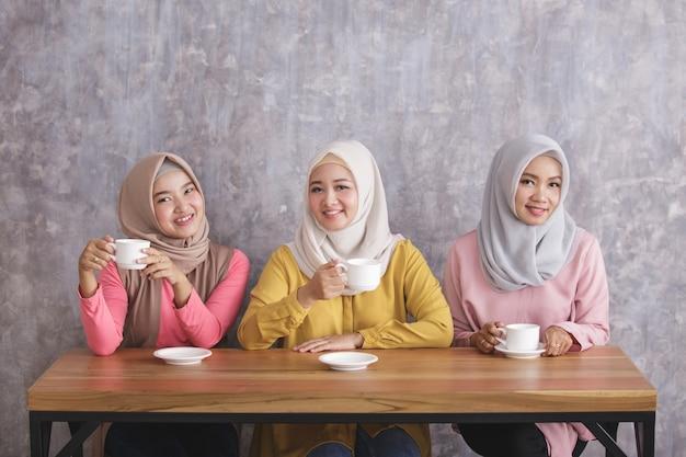 Retrato de tres hermosos hermanos tomando un café juntos en la cafetería.
