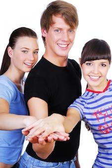 Retrato de tres hermosos jóvenes adultos con las manos apiladas uno encima del otro