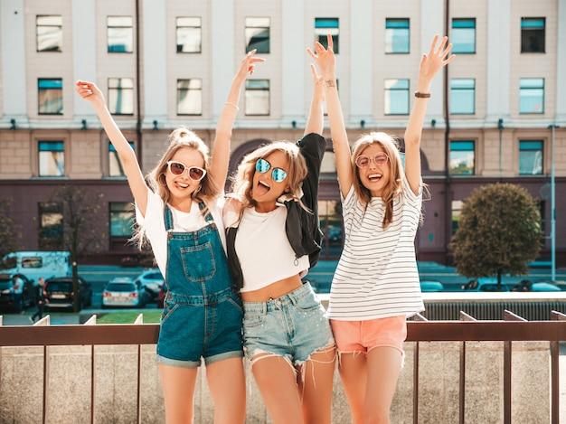 Retrato de tres jóvenes hermosas chicas hipster sonrientes en ropa de moda de verano. mujeres despreocupadas sexy posando en la calle. modelos positivos divirtiéndose en gafas de sol. levantando las manos