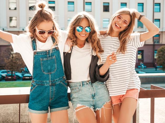 Retrato de tres jóvenes hermosas chicas hipster sonrientes en ropa de moda de verano. mujeres despreocupadas sexy posando en la calle. modelos positivos divirtiéndose en gafas de sol.