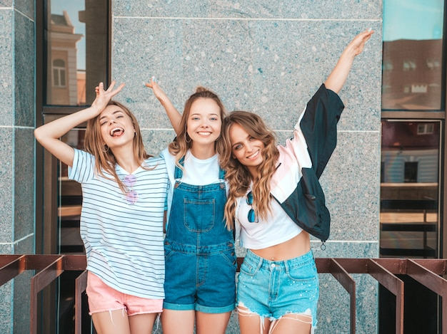 Retrato de tres jóvenes hermosas chicas hipster sonrientes en ropa de moda de verano. mujeres despreocupadas y sexy posando en la calle. modelos positivos divirtiéndose. levantan las manos