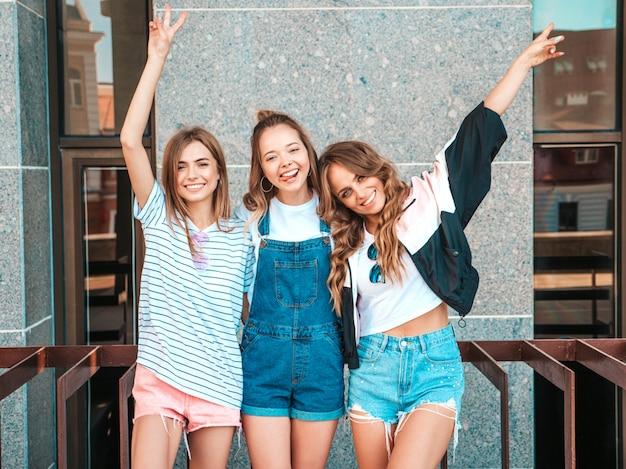 Retrato de tres jóvenes hermosas chicas hipster sonrientes en ropa de moda de verano. mujeres despreocupadas y sexy posando en la calle. modelos positivos divirtiéndose.