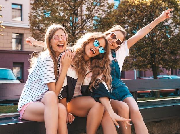 Retrato de tres jóvenes hermosas chicas hipster sonrientes en ropa de moda de verano. mujeres despreocupadas y sexys sentadas en el banco en la calle. modelos positivos divirtiéndose en gafas de sol. levantando las manos