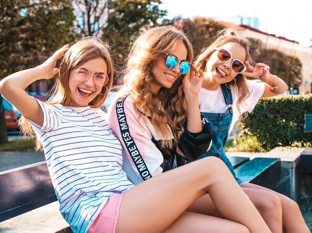 Retrato de tres jóvenes hermosas chicas hipster sonrientes en ropa de moda de verano. mujeres despreocupadas sexys sentadas en el banco en la calle. modelos positivos divirtiéndose en gafas de sol