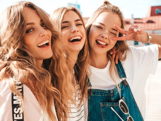 Retrato de tres jóvenes hermosas chicas hipster sonrientes en ropa de moda de verano. sexy mujer despreocupada posando en la calle. modelos positivos divirtiéndose