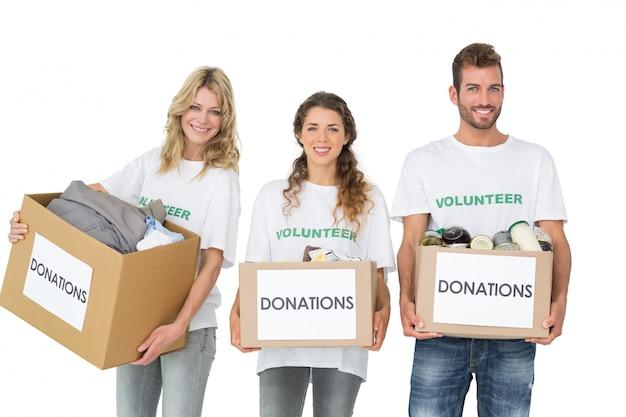 Retrato de tres jóvenes sonrientes con cajas de donación