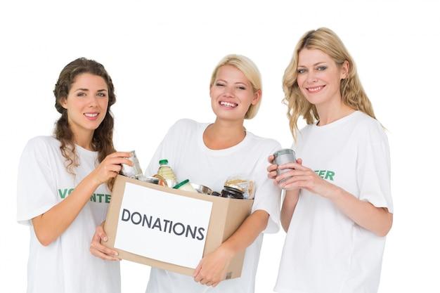 Retrato de tres mujeres jóvenes sonrientes con caja de donación