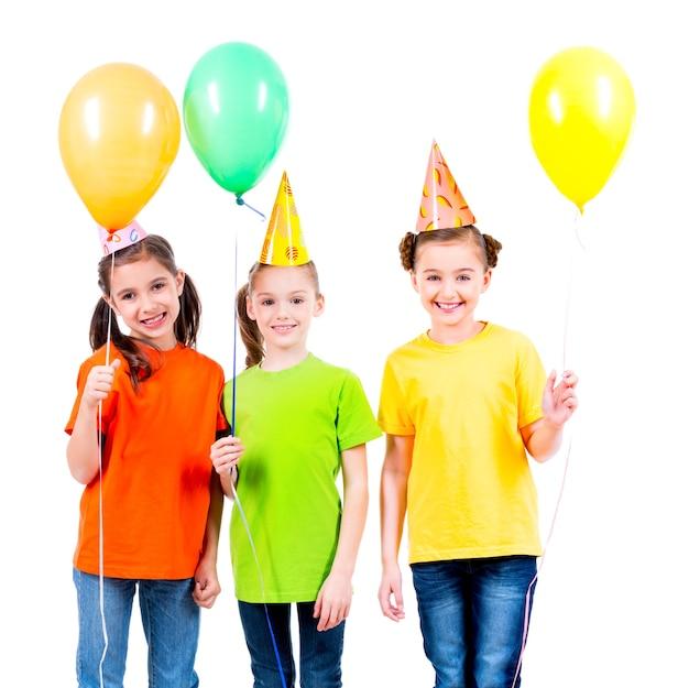 Retrato de tres niñas lindas con globos de colores y gorro de fiesta, aislado en blanco.