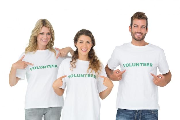Retrato de tres voluntarios felices apuntando a sí mismos