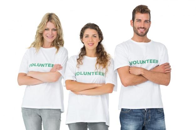 Retrato de tres voluntarios felices de pie con las manos cruzadas