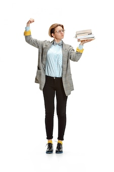 Retrato de una triste estudiante sosteniendo libros aislados en pared blanca