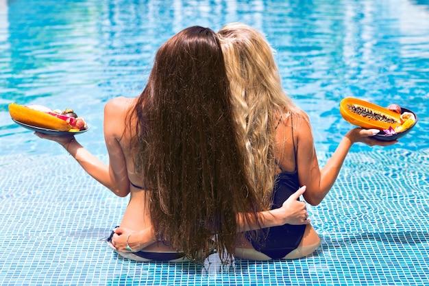 Retrato tropical de vacaciones a dos chicas lentas, con increíbles pelos largos rubios y morenas, sentadas de espaldas a la cámara, con bikinis de falta posando en la piscina sosteniendo platos con frutas exóticas