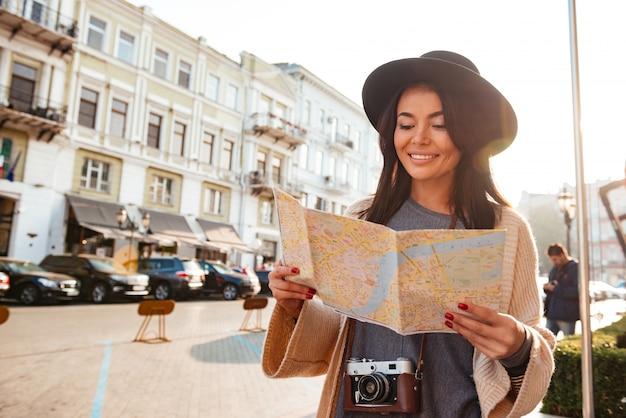 Retrato de un turista sonriente mujer sosteniendo mapa de la ciudad