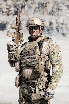 Retrato de ubicación de media longitud de gran soldado musculoso en uniformes de campo con rifle en el desierto entre rocas