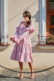 Retrato urbano al aire libre de joven hermosa chica elegante en vestido rosa de gran tamaño