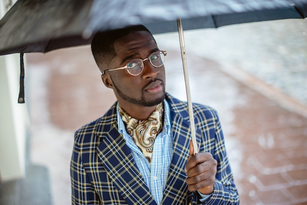 Retrato urbano del apuesto hombre de negocios afroamericano de pie en el centro de la ciudad en tiempo nublado bajo un paraguas negro vestido con ropa formal.