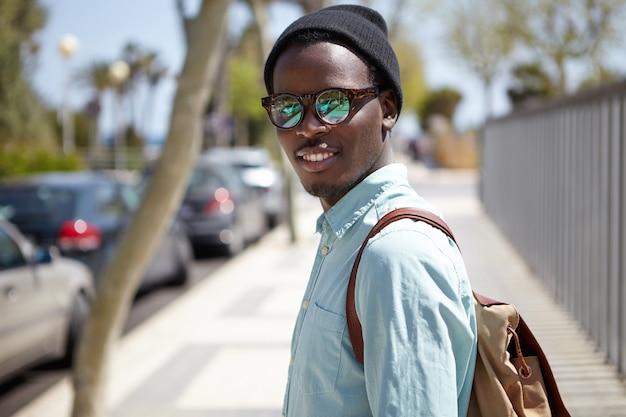Retrato urbano de verano de guapo hombre afroamericano de aspecto moderno con gafas y sombrero caminando en las calles de una ciudad extranjera, haciendo turismo, visitando puntos de referencia mientras pasa vacaciones en el extranjero