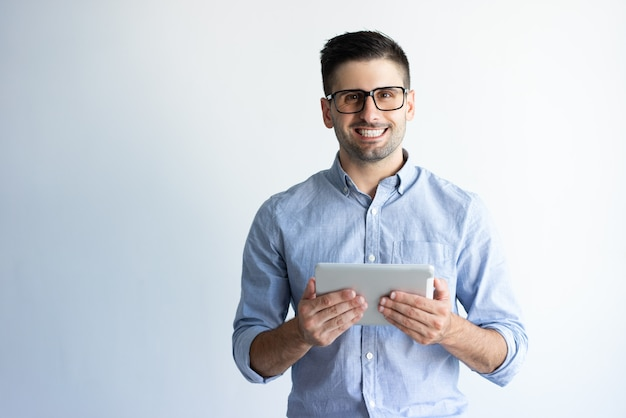 Retrato del usuario emocionado alegre de la tableta que lleva las lentes