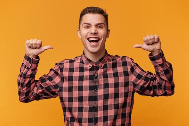 Retrato de un vano hombre feliz jactancioso en camisa de mezclilla apretando los puños como ganador y señalando con el pulgar sobre sí mismo