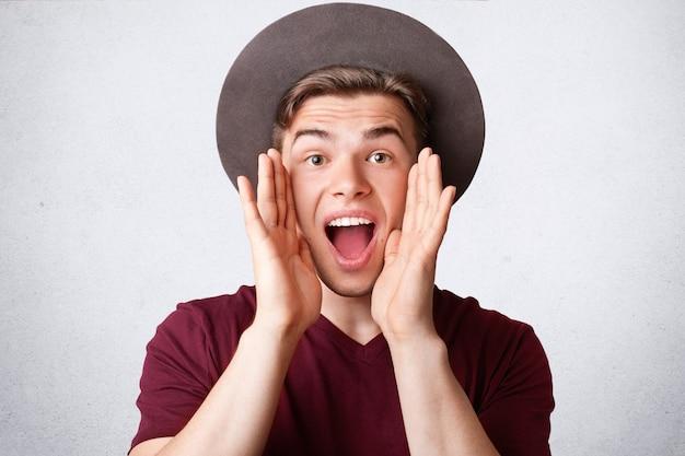 El retrato del varón caucásico feliz exclama alegremente, mantiene la boca abierta, viste un elegante sombrero y camiseta, estando en alto espíritu, aislado sobre fondo blanco. concepto de personas, positividad y estilo de vida