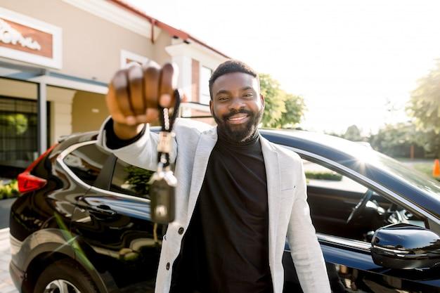 Retrato del vendedor de automóviles del hombre africano que sostiene llaves del coche. atractivo alegre joven africano sonriendo mostrando las llaves del auto a su nuevo auto posando al aire libre en el salón del concesionario