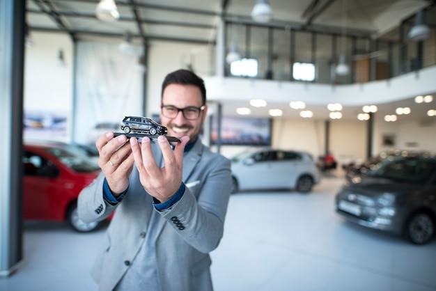 Retrato de vendedor de coches profesional con vehículo de juguete en la sala de exposición del concesionario de coches.