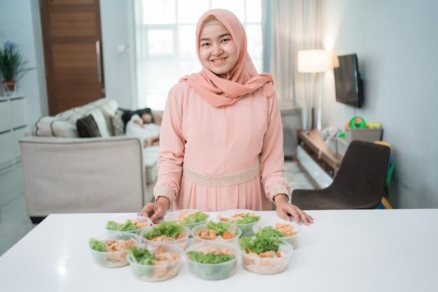 Retrato de vendedor de comida de mujer musulmana asiática preparando su producto en la cocina de casa