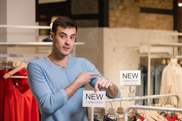 Retrato de vendedor sonriente apuntando al cartel blanco con nuevas palabras de colección en la mano en la tienda de ropa