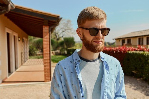 Retrato de verano al aire libre de apuesto joven europeo barbudo macho