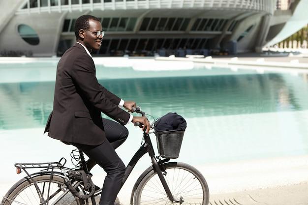 Retrato de verano al aire libre de un guapo joven oficinista europeo negro con gafas de sol en bicicleta en su bicicleta para trabajar en un entorno urbano, divertirse, sentirse despreocupado y relajado