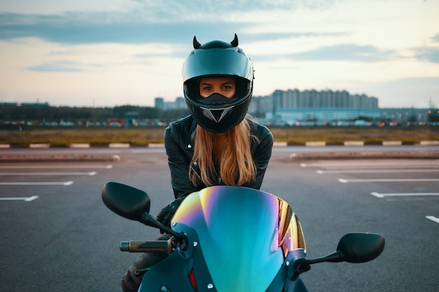 Retrato de verano al aire libre de hermosa mujer joven feliz con casco de motocicleta de seguridad y chaqueta de cuero listo para paseo nocturno