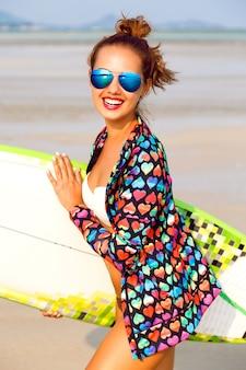 Retrato de verano al aire libre de mujer sonriente corriendo con tabla de surf cerca del océano azul
